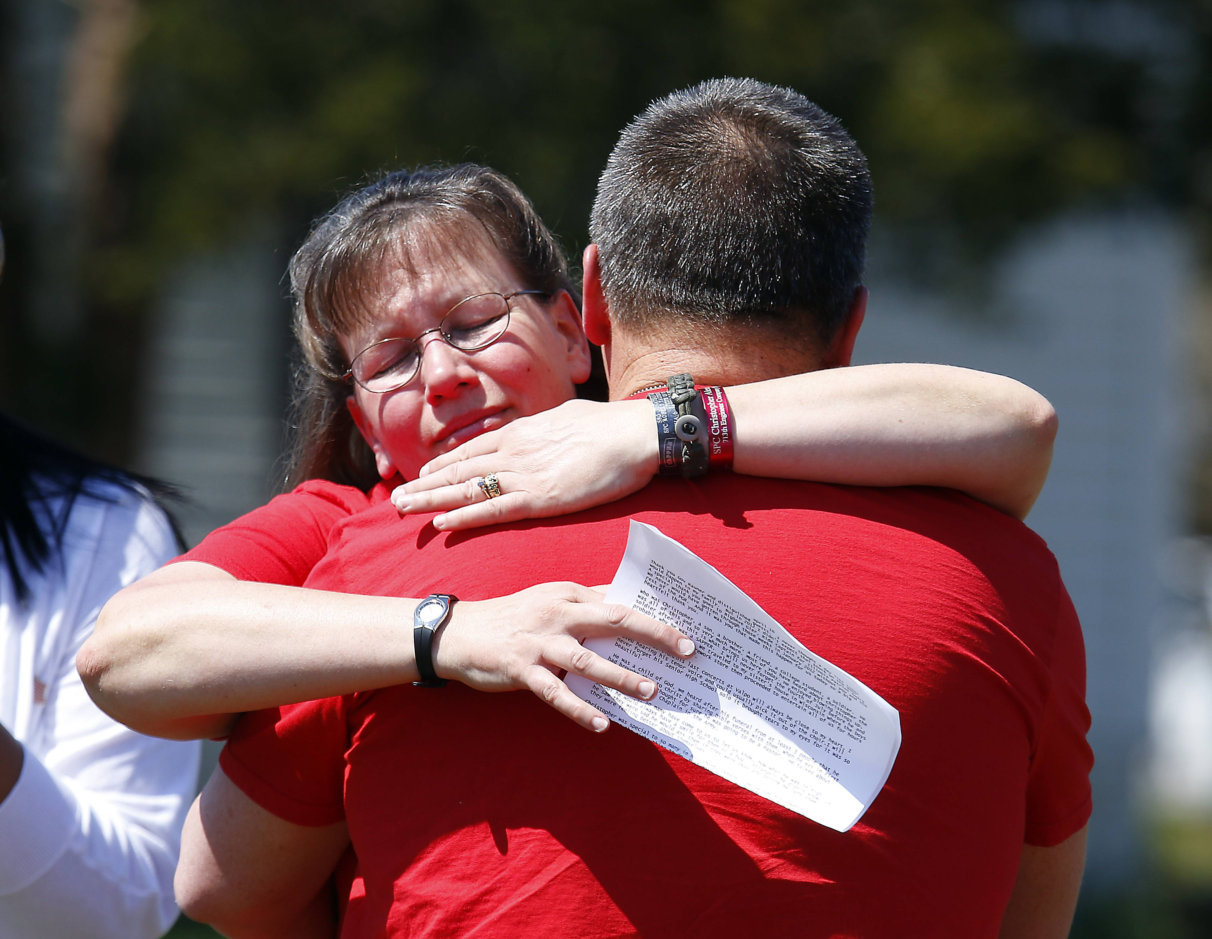 Mary Patterson hugs Bob Patterson after talking about their son Spc. Christopher Patterson Saturday. Route 31 in North Aurora was dedicated and renamed in honor of Spc. Christopher Patterson who died in Afghanistan in January 2012.