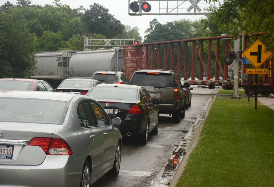 Cars wait for a freight train to pass on Route 14 in Barrington. A proposal would send freight trains on a massive new railroad route outside the entire suburban area.