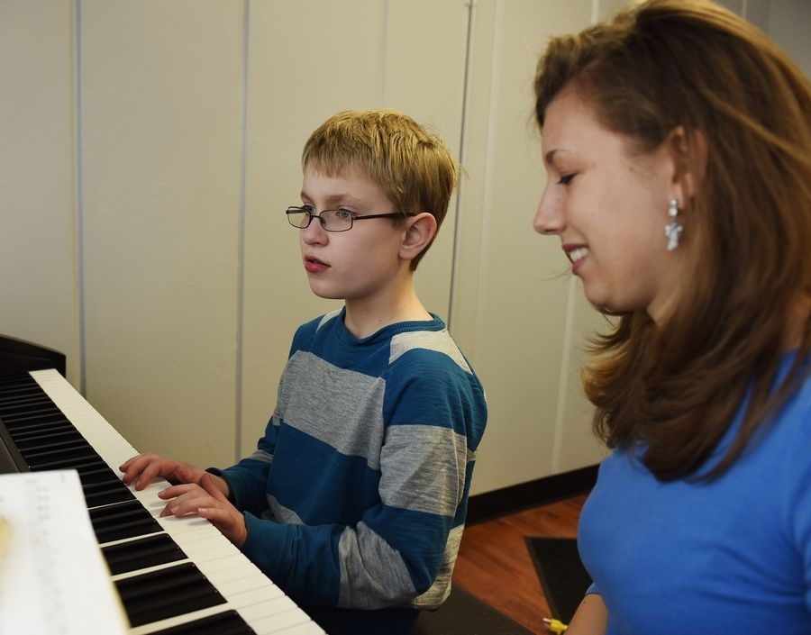 Aidan McCurley, 10, of Palatine, who is on the autism spectrum, plays piano during a recent lesson with Alexis Ross of Arlington Heights. Ross teaches piano to more than 20 students with special needs, including McCurley.