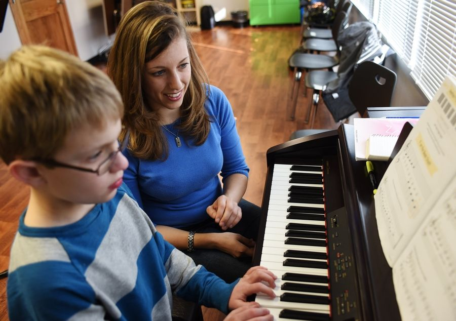 Alexis Ross of Arlington Heights teaches piano to more than 20 students with special needs, including Aidan McCurley, 10, of Palatine, who is on the autism spectrum. McCurley is playing during a recent lesson in Rolling Meadows.
