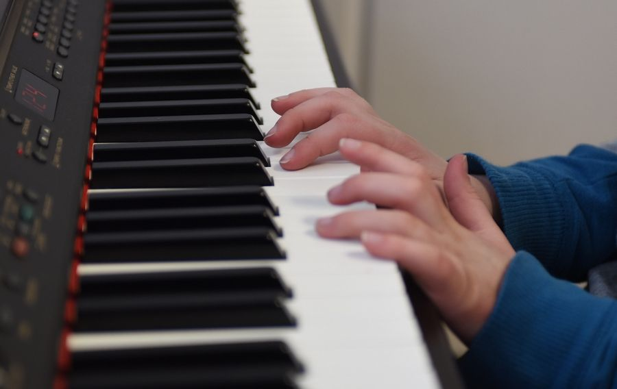 Aidan McCurley, 10, of Palatine, who is on the autism spectrum, plays piano during a lesson with Alexis Ross of Arlington Heights.