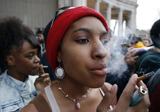 Destiny Sneed smokes marijuana during the annual 4/20 marijuana gathering at Civic Center Park in downtown Denver, Wednesday, April 20, 2016. Public consumption remains illegal under the state's recreational pot law, which was passed in 2012, but police mostly looked on as a cloud of marijuana smoke rose above the crowd.