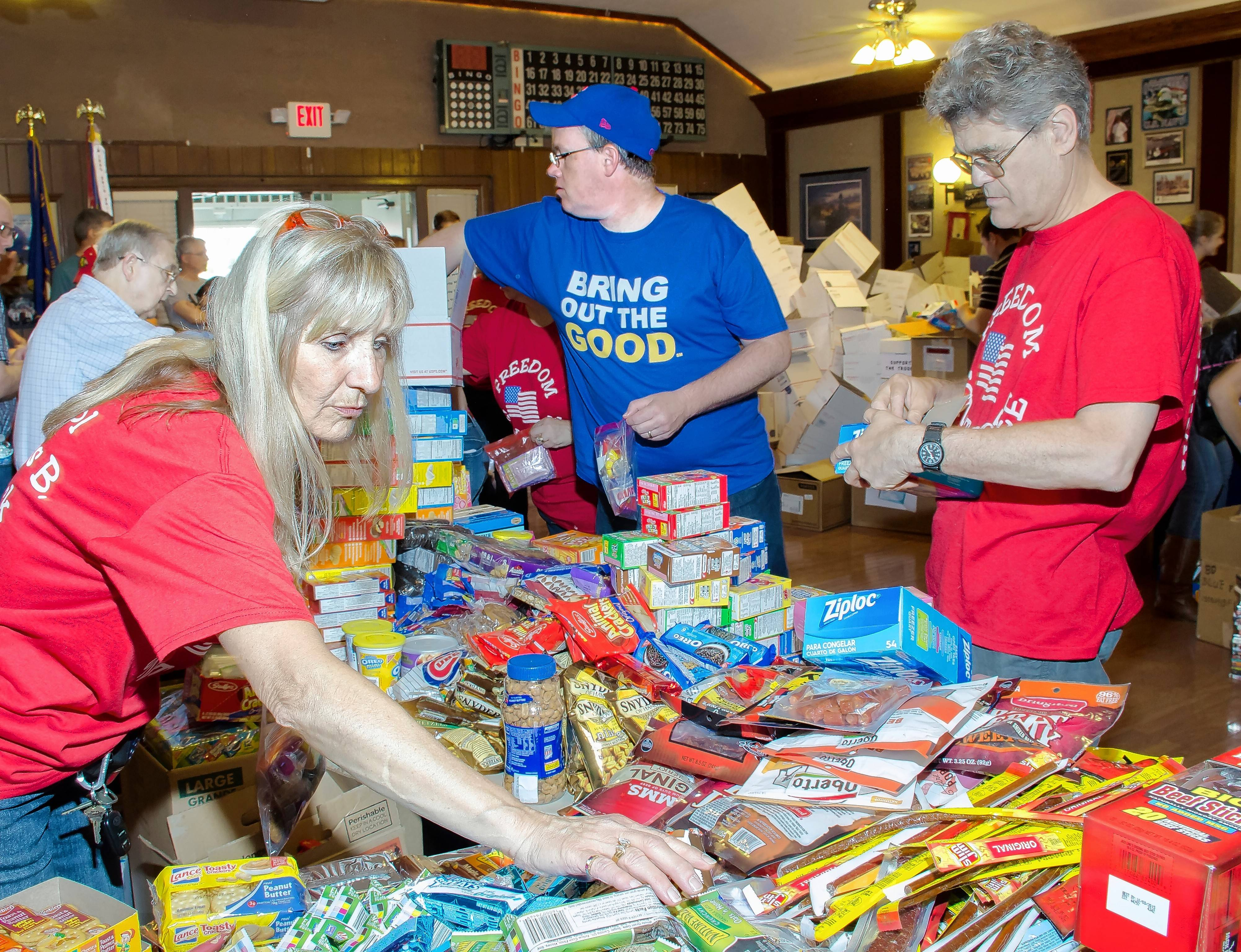 Volunteers with Help USA pack boxes to be shipped overseas. The 2016 packing project will commence at 11 a.m. Sunday, at the AMVETS Post 66 in Wheeling.