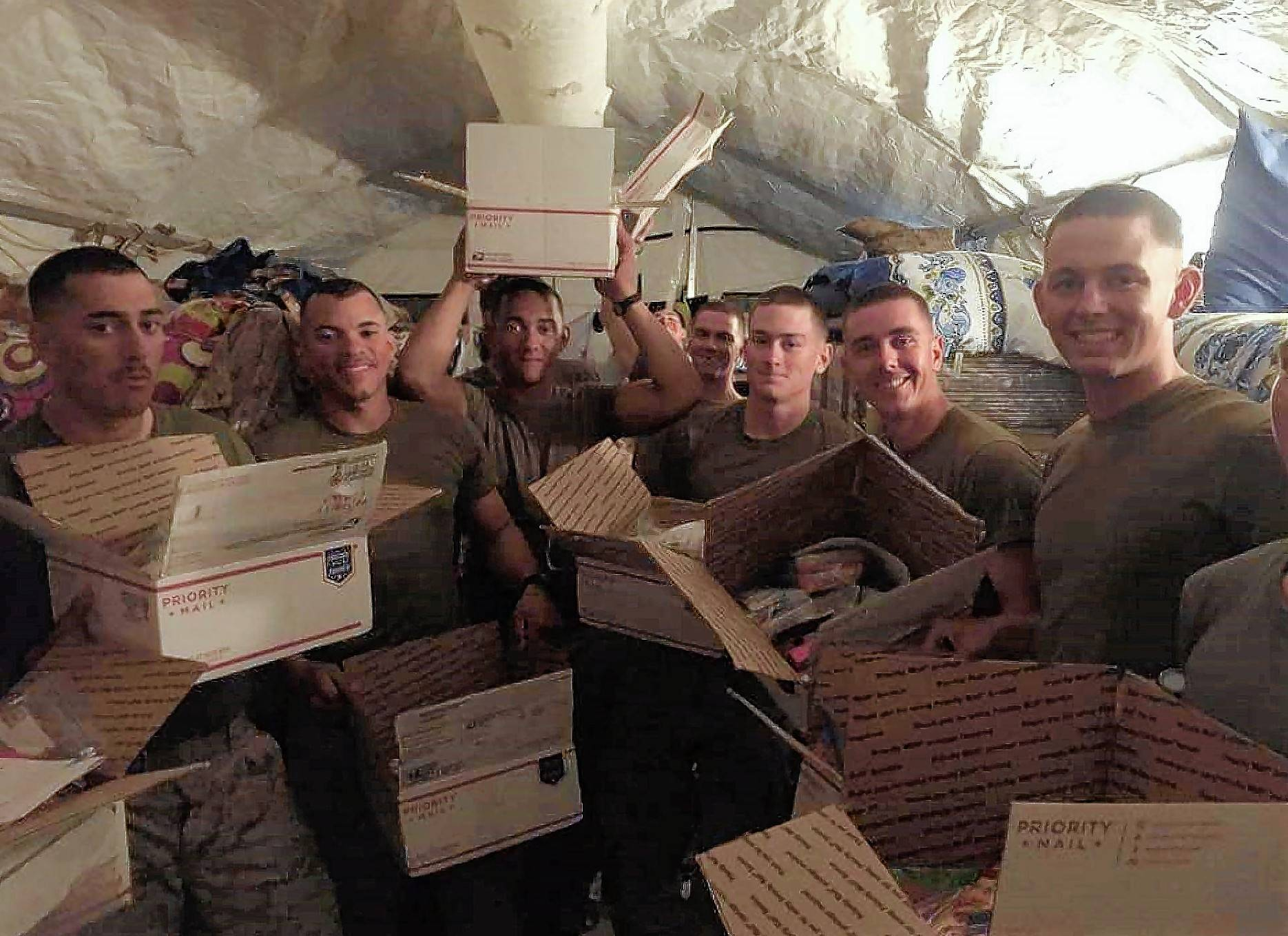 Marines overseas in an unspecified location, opening the boxes of goodies sent by Help USA Troops.
