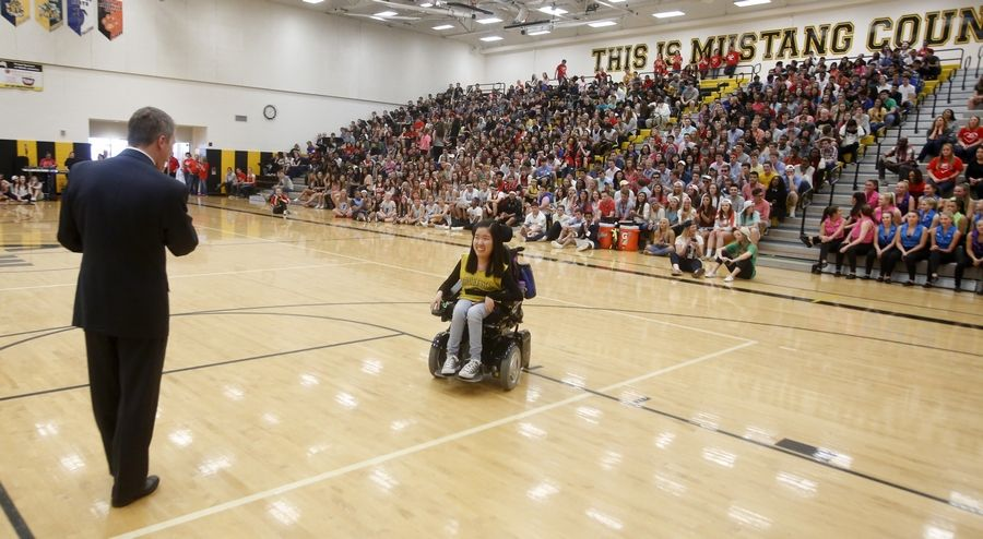 Metea Valley High School junior Jungin Angie Lee comes forward during a pep assembly to receive the Prudential Spirit of Community Award, recognizing her as the top high school volunteer in the state.