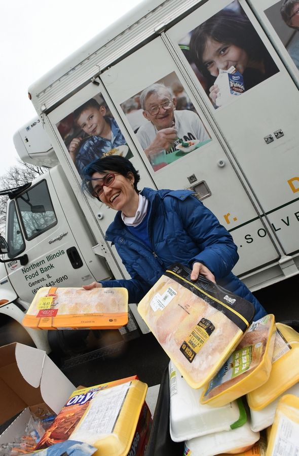 Terese Janik of Winfield sorts food from a Northern Illinois Food Bank mobile food pantry stationed at Lowell Elementary in Wheaton.