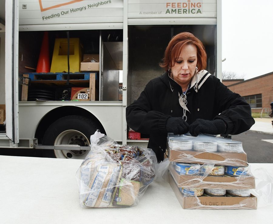 Karen Rood of Winfield unpacks cans of chicken during a mobile food pantry visit to Lowell Elementary in Wheaton.