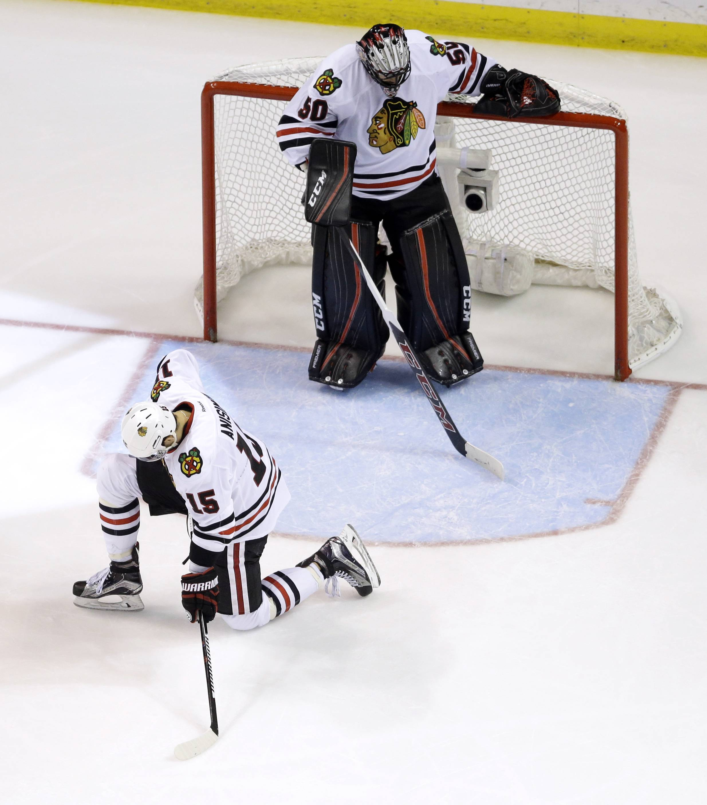 Chicago Blackhawks goalie Corey Crawford, top, and teammate Artem Anisimov, of Russia, pause after allowing a goal by St. Louis Blues' Troy Brouwer during the third period in Game 7 of an NHL hockey first-round Stanley Cup playoff series Monday, April 25, 2016, in St. Louis. The Blues won 4-3 to take the series 4-3.