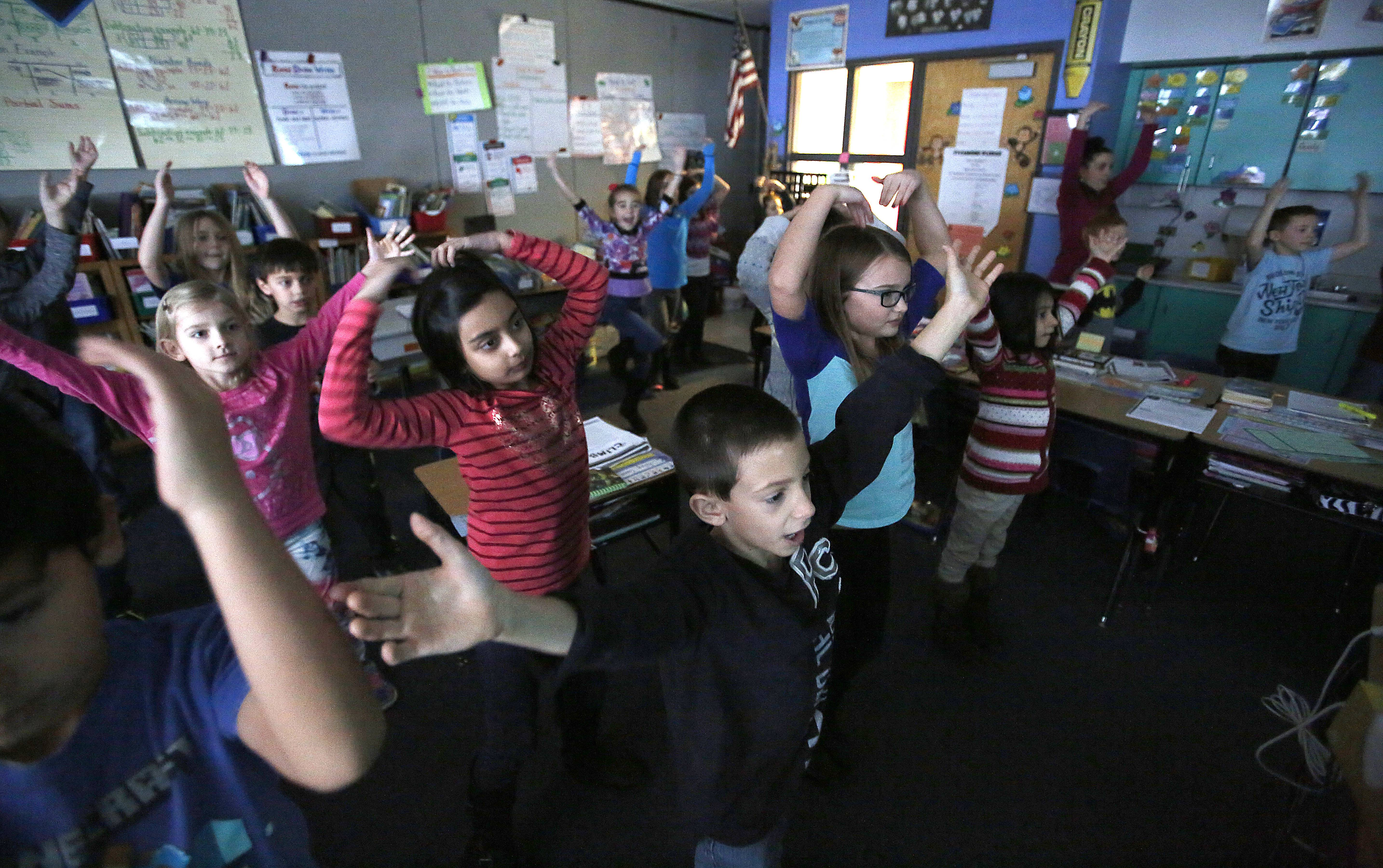 "In Tarren Cedillo's second-grade classroom at Sycamore Trails Elementary School in Bartlett, students get some movement in between academic lessons. Riley Gavin, 7, center, and classmates perform the song ""YMCA"" and dance during an afternoon class. It's part of the school's use of the online program GoNoodle."