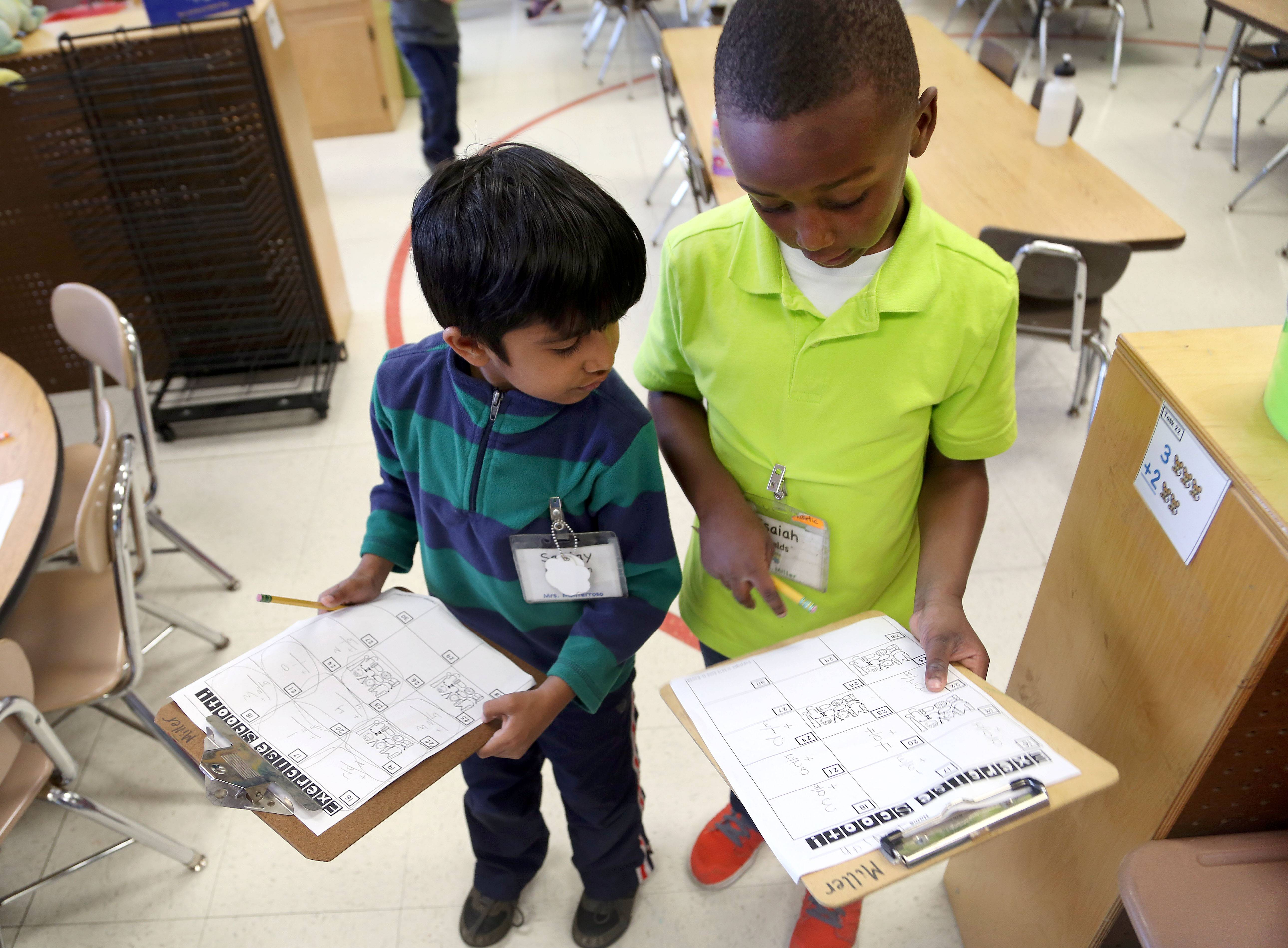 Kindergartners Sanjay Madhavan, left, and Isaiah Fields work on a project involving math problems and exercise as kids at Woodland Primary School spent the day observing Earth Day Friday in Gages Lake.
