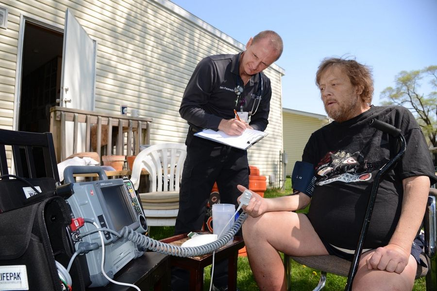 Advocate Sherman Hospital paramedic Ken Snow paid a home visit Monday to Tim Youngberg in Elgin as part of the hospital's mobile integrated health care program.