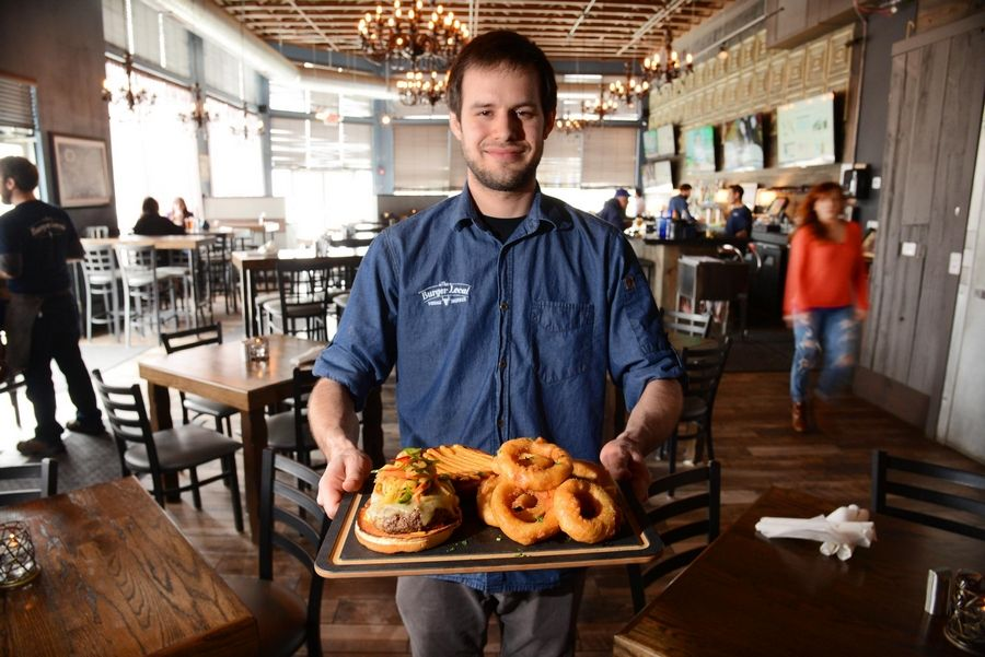Executive chef Eric Olson shows off the beef brisket burger, a recent Burger of the Week, and beer-battered onion rings at the vintage-inspired The Burger Local in Geneva.
