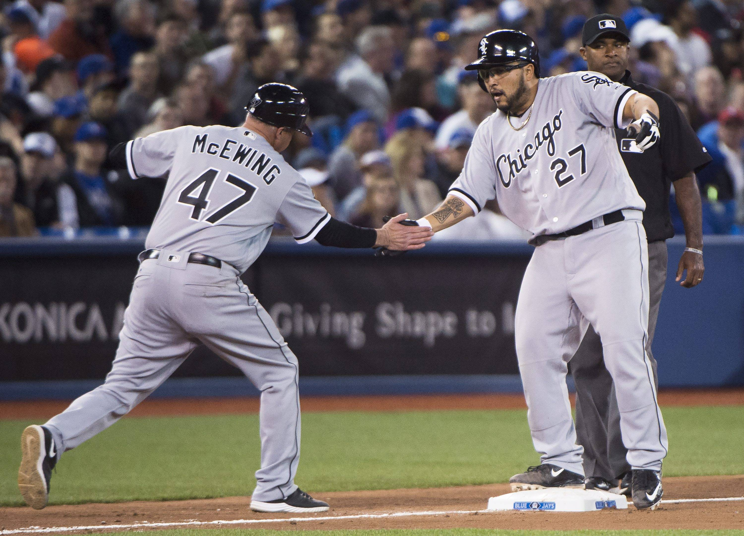 Chicago White Sox catcher Dioner Navarro (27) celebrates with third base coach Joe McEwing (47) after hitting a two-run triple against the Toronto Blue Jays during the seventh inning of a baseball game Wednesday, April 27, 2016, in Toronto. (Nathan Denette/The Canadian Press via AP)