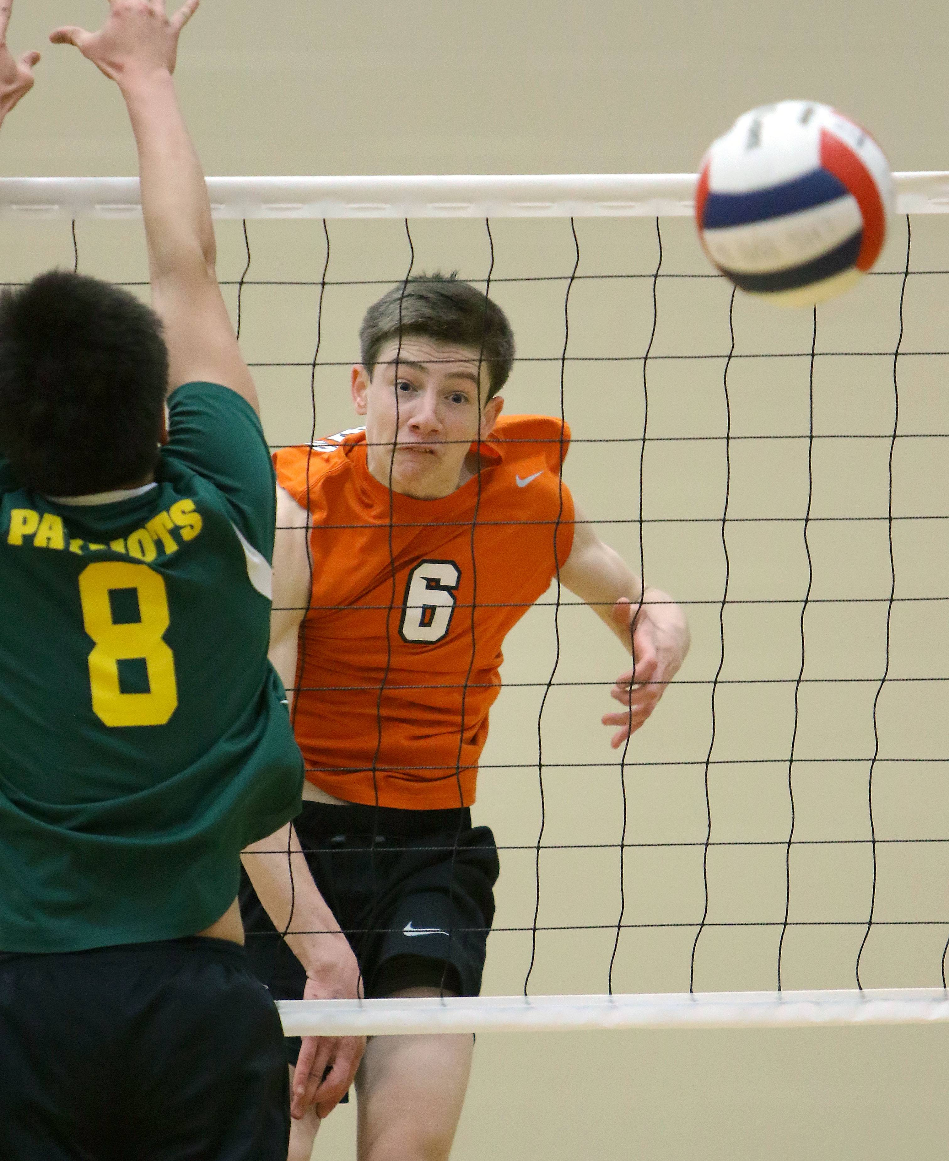 Libertyville's Jack Stevens, left, spikes one past Stevenson's Jeffrey Wang on Wednesday at Libertyville.
