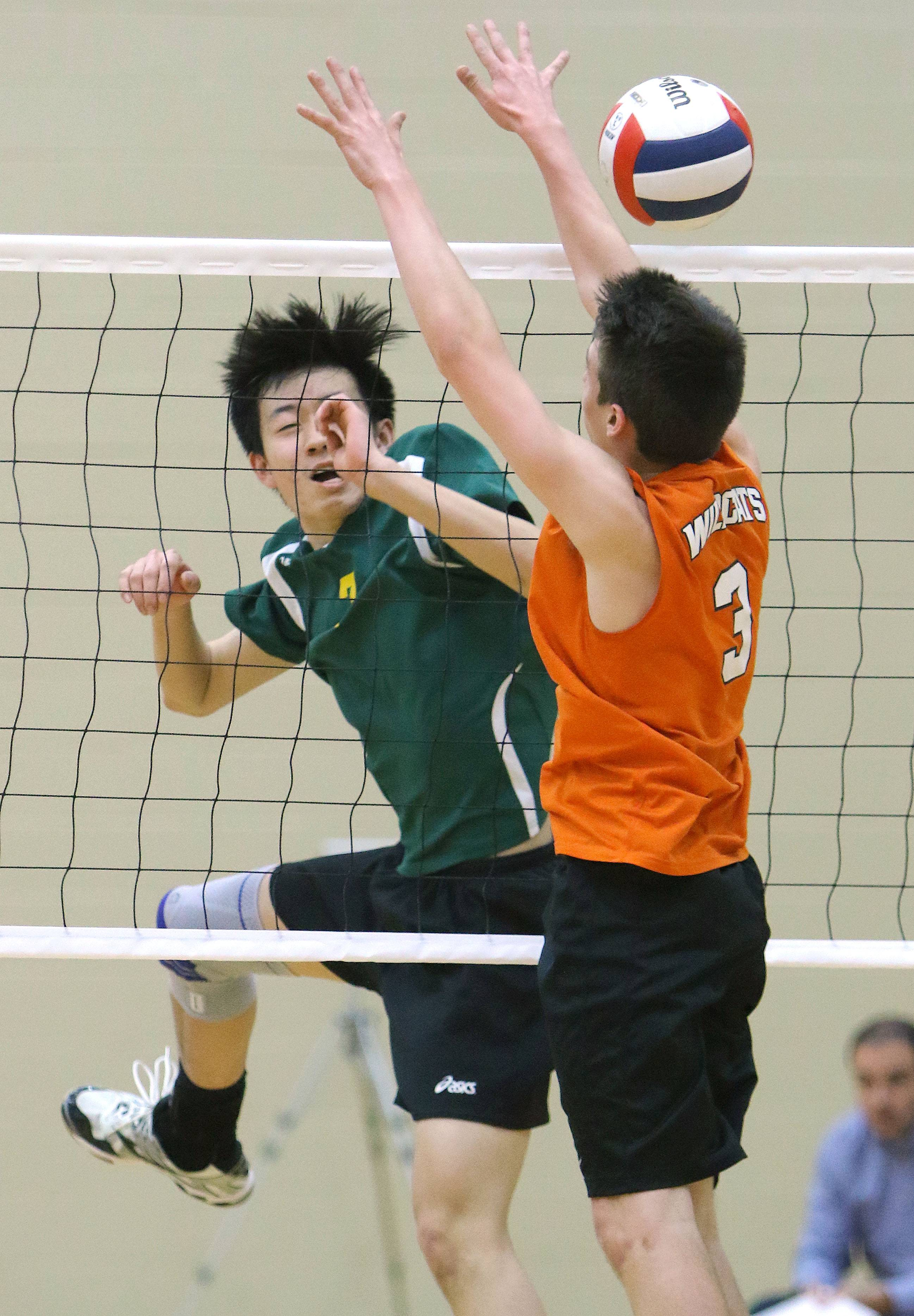 Stevenson's Leo Chen, left, and Libertyville's Ryan Hirschel meet at the net during their game Wednesday at Libertyville.