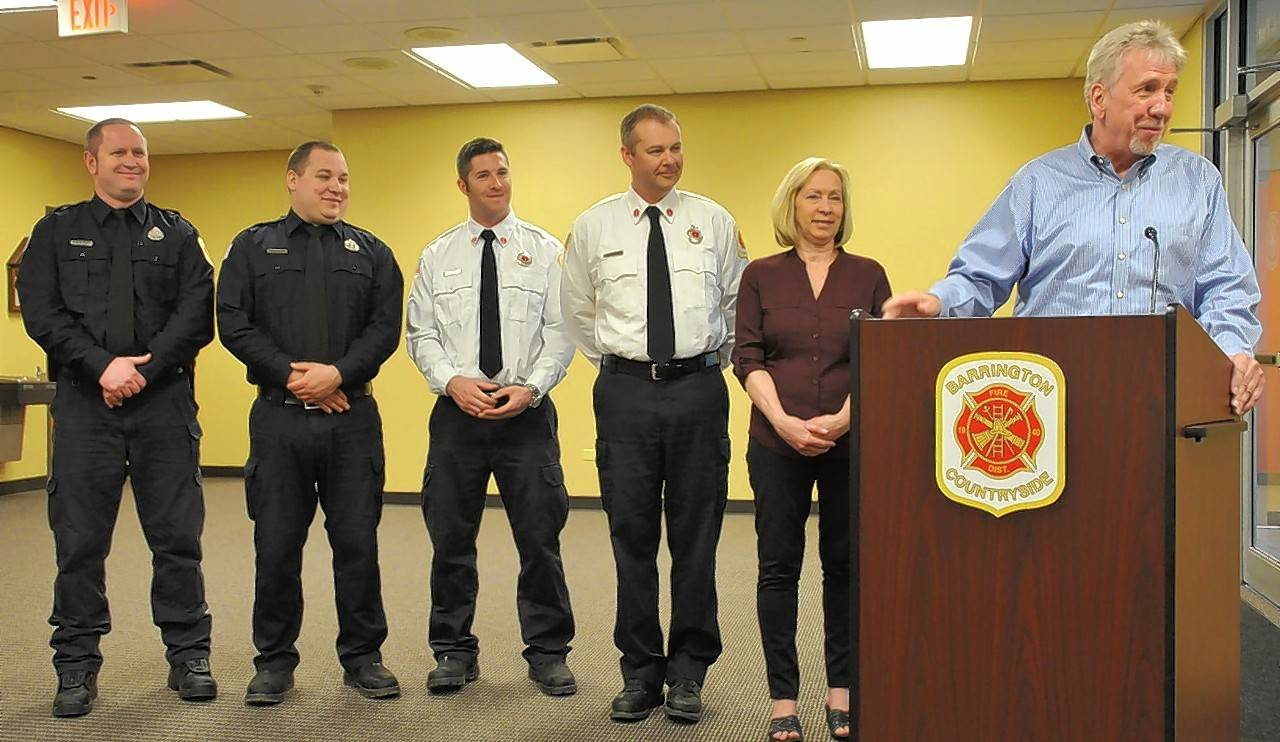 Gary Stromberg, at podium, thanked the Barrington Countryside Fire Protection District firefighters who saved his life on Christmas Eve last year, including (from left to right) Lts. Brett Haller and Kyle Racina, and firefighter/paramedics Justin Kenyon and Mike DeLillo. Next to Stromberg is his wife, Laura.