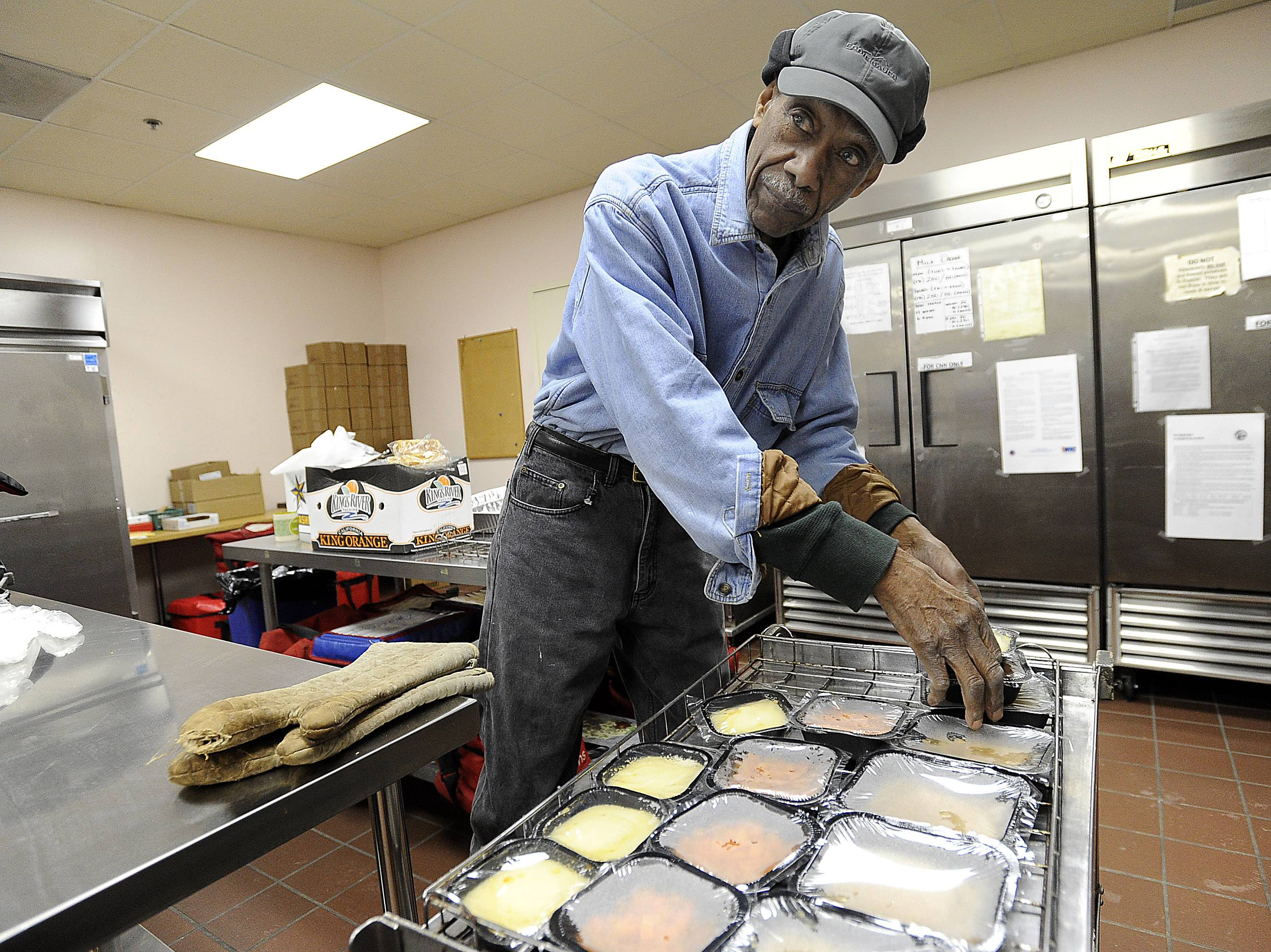 Meals on Wheels driver Samuel Grimes, 88, prepares hot meals for his delivery route. In DuPage County, the Senior Citizens Council was able to continue its meal service despite receiving no state money by closing their community dining sites. The community dining services are set to reopen in May.