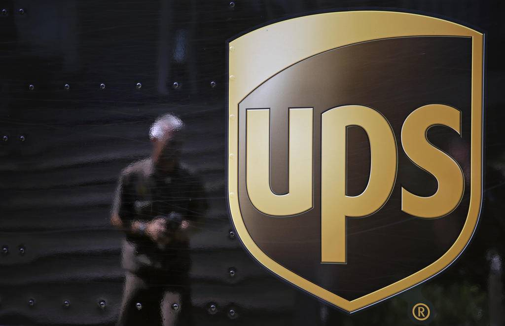 FILE - In this June 20, 2014, file photo, the United Parcel Service logo is seen on the side of a truck as driver Marty Thompson is reflected returning from a delivery in Cumming, Ga. United Parcel Service Inc. is scheduled to report financial results on Thursday, April 28, 2016. (AP Photo/David Goldman, File)