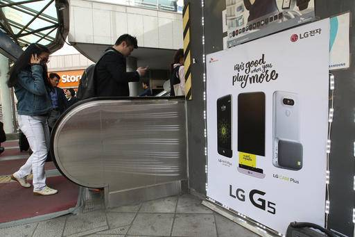 People pass by a poster advertising LG Electronics' G5 smartphone at Seoul Railway Station in Seoul, South Korea, Thursday, April 28, 2016. LG Electronics Inc. reported a stunning jump in its first-quarter earnings as its high-end home appliance sales offset a loss for its smartphone business. (AP Photo/Ahn Young-joon)