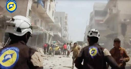 FILE - In this Sunday, April 24, 2016, file photo made from video posted online by the Syrian Civil Defense White Helmets, Civil Defense workers run after airstrikes and shelling hit Aleppo, Syria. A military buildup in northern Syria coupled with heavy fighting and mounting civilian casualties spells the end of a cease-fire that for two months brought much needed relief to war-stricken Syrians, ushering in what could be an even more ruinous chapter in the country's five-year-old conflict. (Syrian Civil Defense White Helmets via AP video, File)