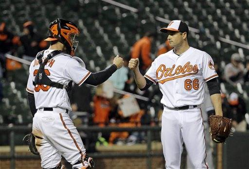 Baltimore Orioles catcher Caleb Joseph, left, and relief pitcher T.J. McFarland celebrate after closing out a baseball game against the Chicago White Sox in Baltimore, Thursday, April 28, 2016. Baltimore won 10-2. (AP Photo/Patrick Semansky)