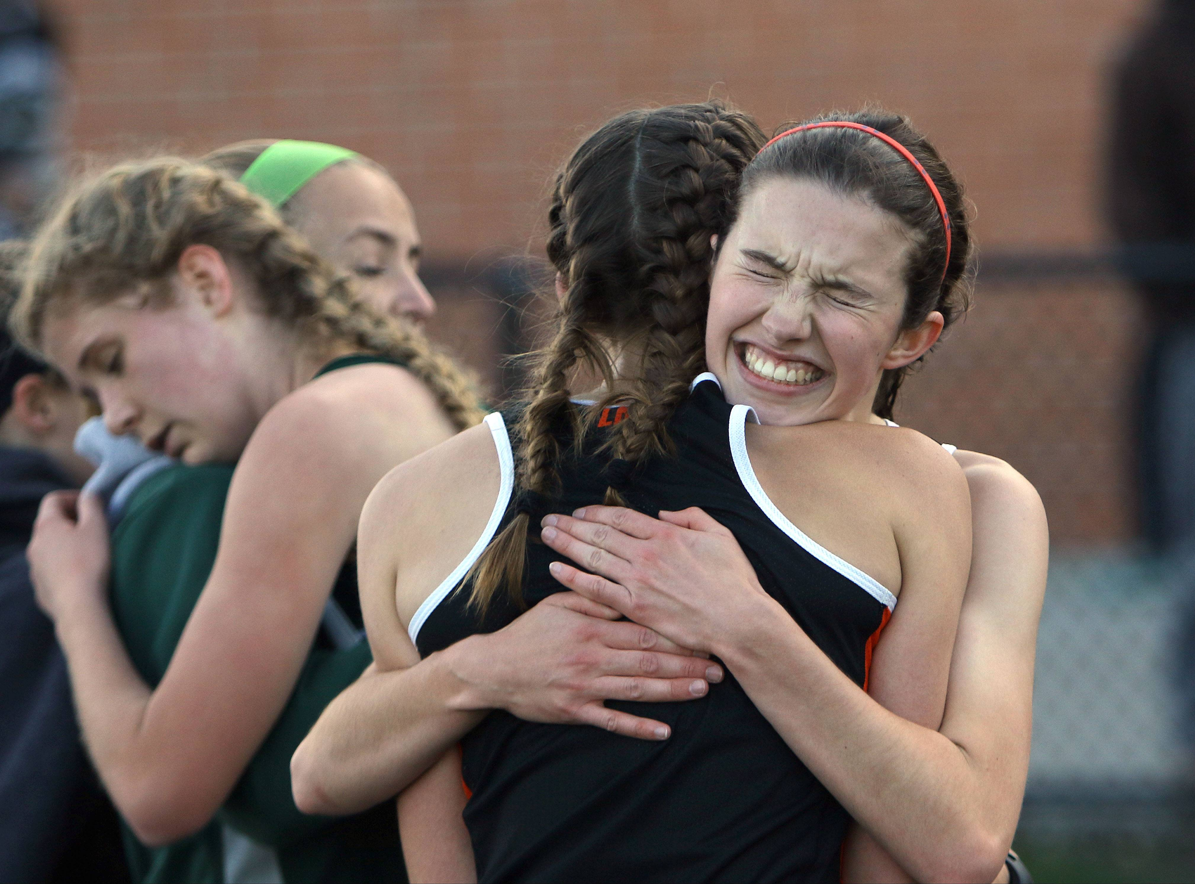 Libertyville's Melissa Manetsch, right, hugs Sarah Townsend after winning the 3,200-meter run during the Lake County meet Friday at Grayslake North High School.