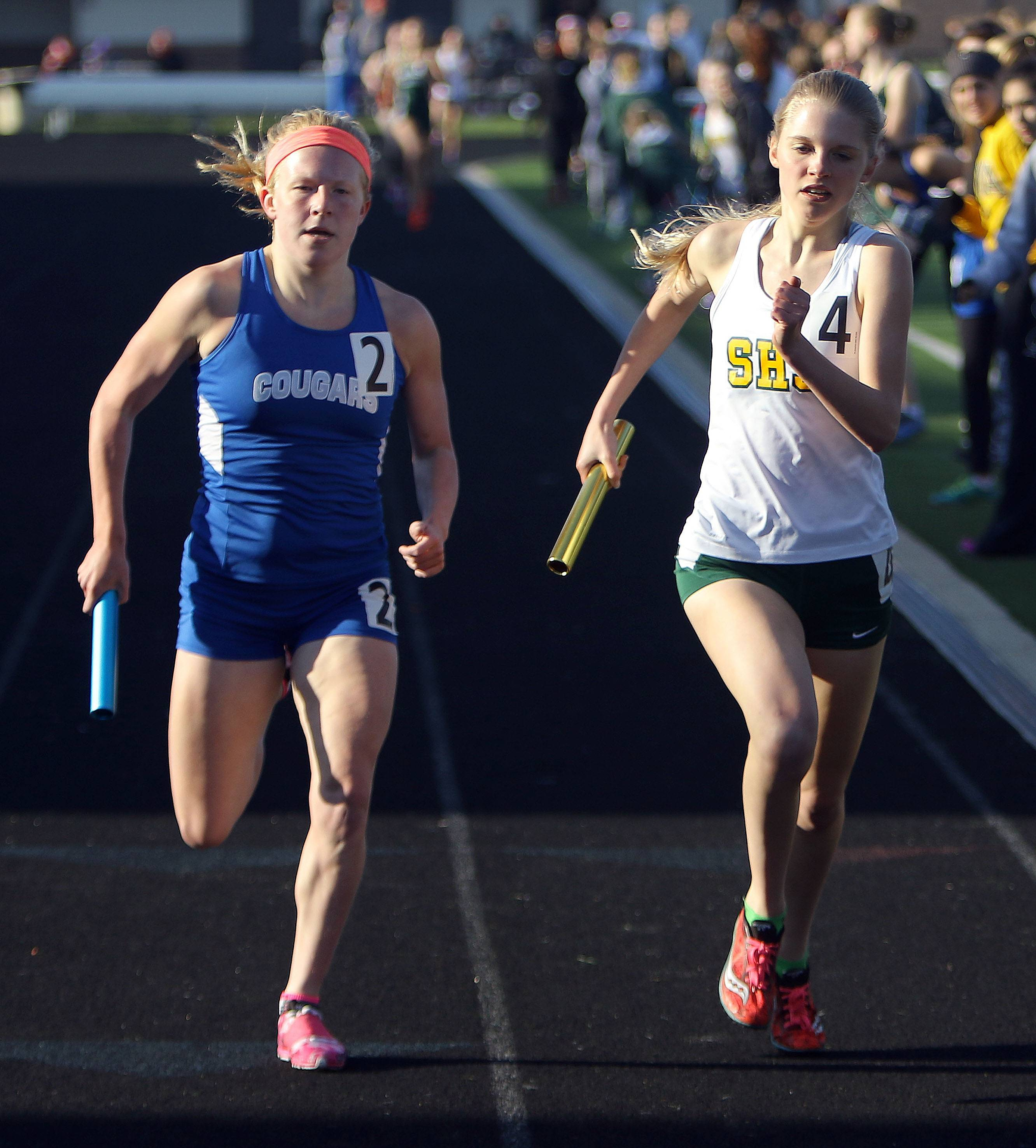 Vernon Hills' Nicole Pinter, left, and Stevenson's Isabelle Sparreo sprint to the finish in the 4x800 relay during the Lake County meet Friday at Grayslake North High School.