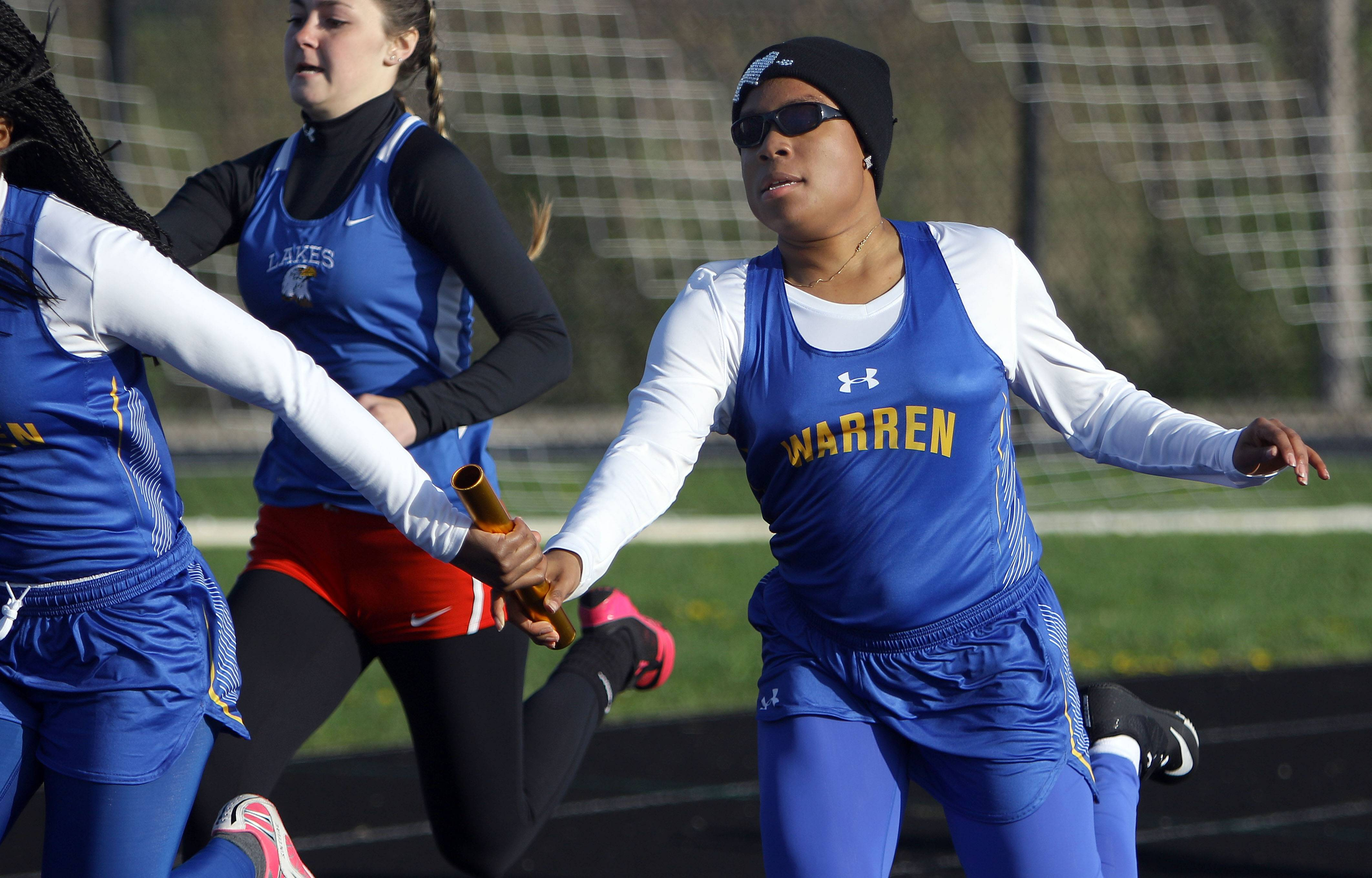 Warren's Jasmine Ward, right, hands the baton to Ciana Washington during the Lake County meet Friday at Grayslake North High School.
