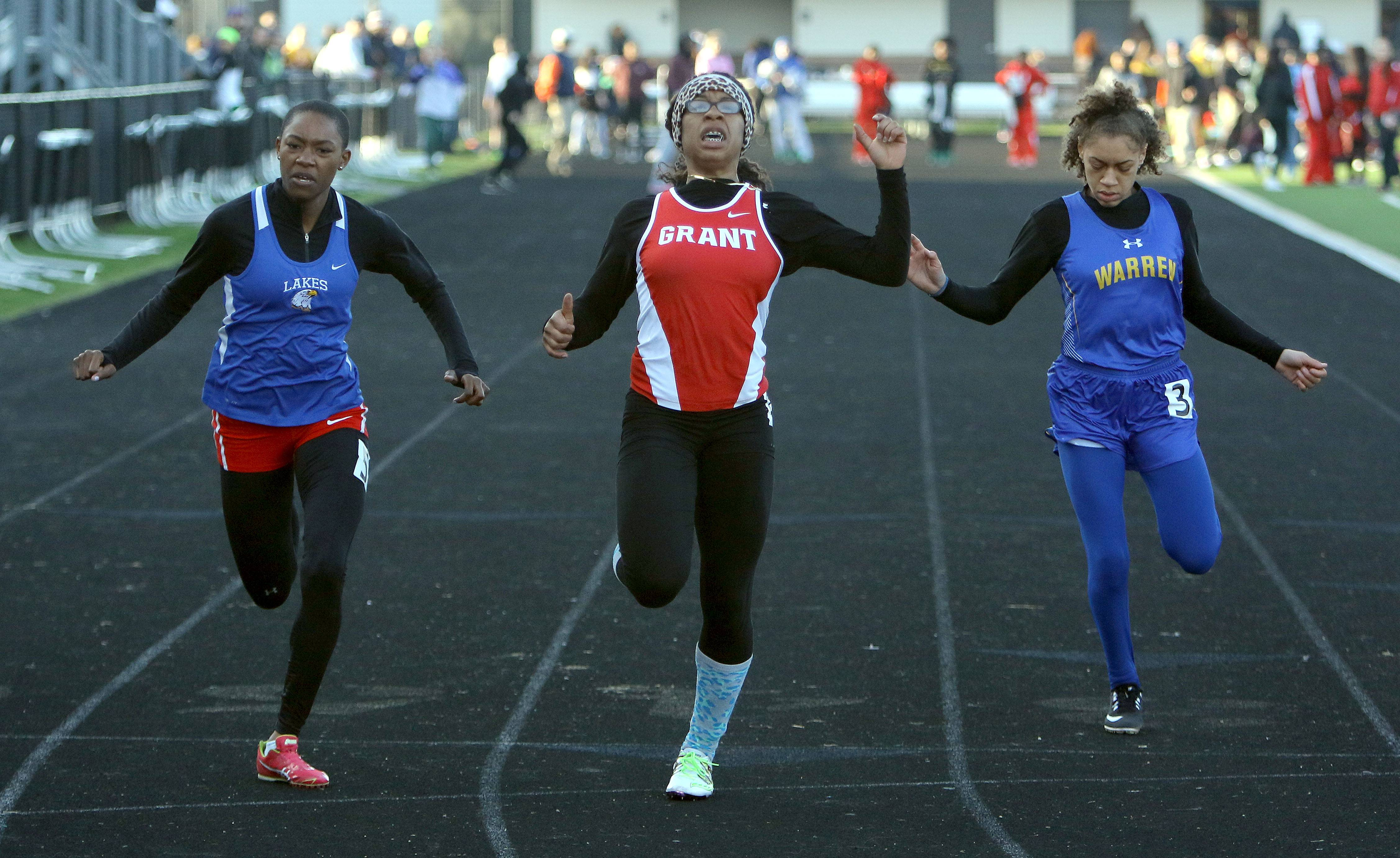 From left, Lakes' Taylor Tilman, Grant's Ariyona Wallace and Warren's Janii Jenkins cross the finish in the 100-meter dash during the Lake County girl track meet Friday at Grayslake North High School.