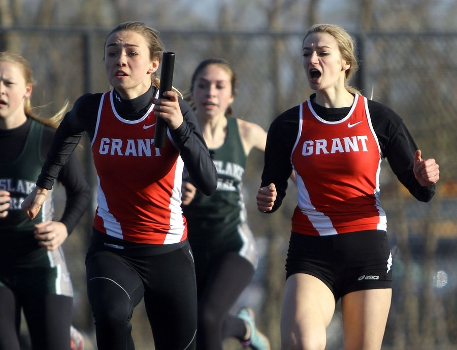 Grant's Delaney Basala, left, hands the baton to Morgan Race in the 4x100 relay during the Lake County meet Friday at Grayslake North High School.