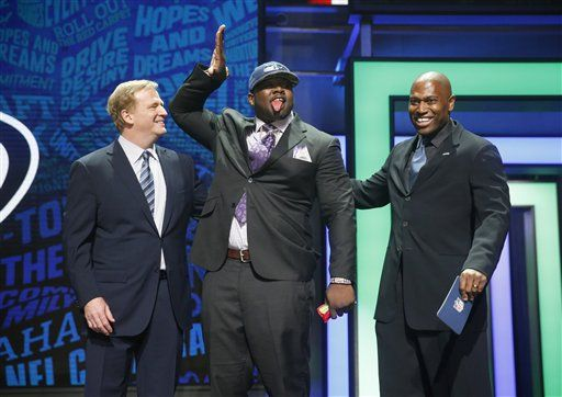 Alabama's Jarran Reed poses for photos with NFL Commissioner Roger Goodell, left, and former NFL player Shaun Alexander after being selected by the Seattle Seahawks as the 49th pick in the second round of the 2016 NFL football draft, Friday, April 29, 2016, in Chicago.
