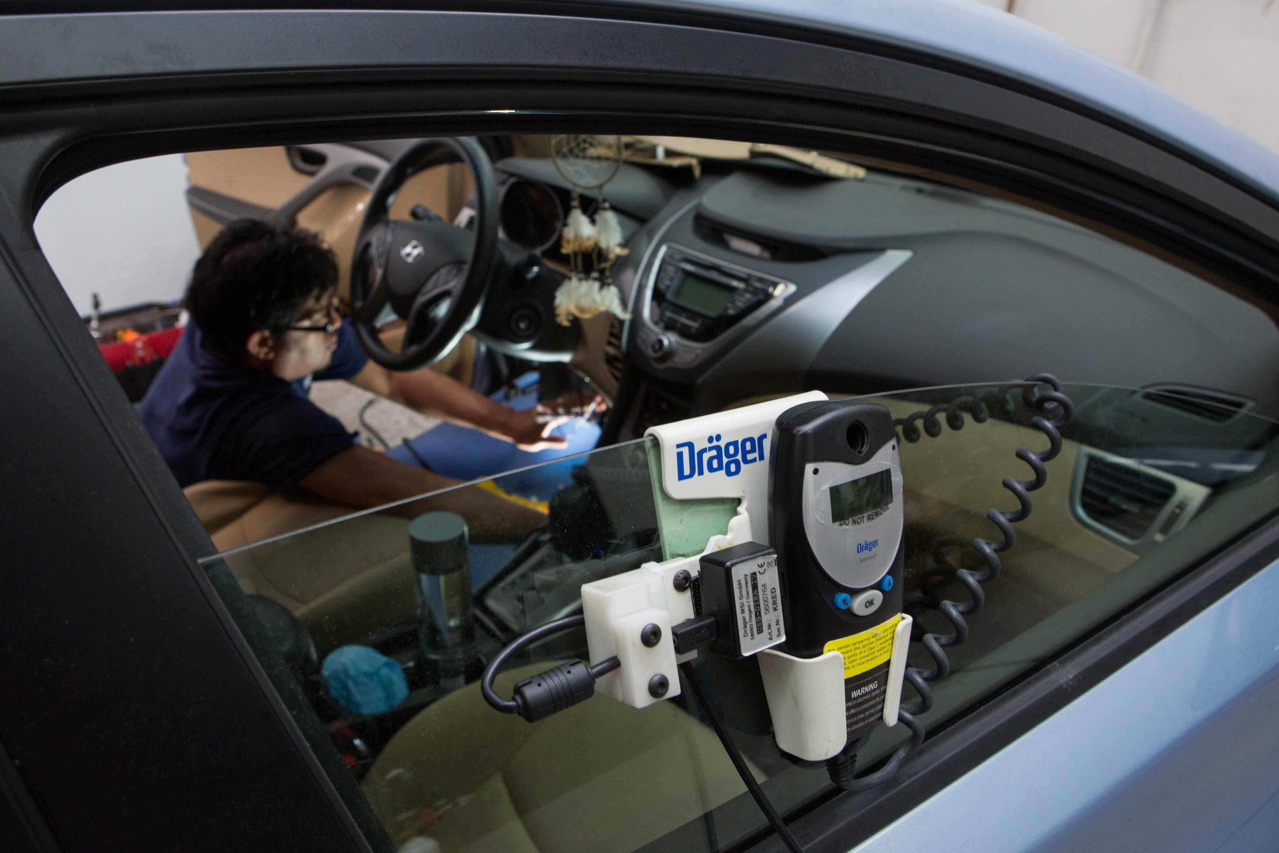 Technician Gabriel Cajchun works with an ignition interlock device at an Alexandria service center. The device is designed to keep drunk drivers from operating their vehicles.
