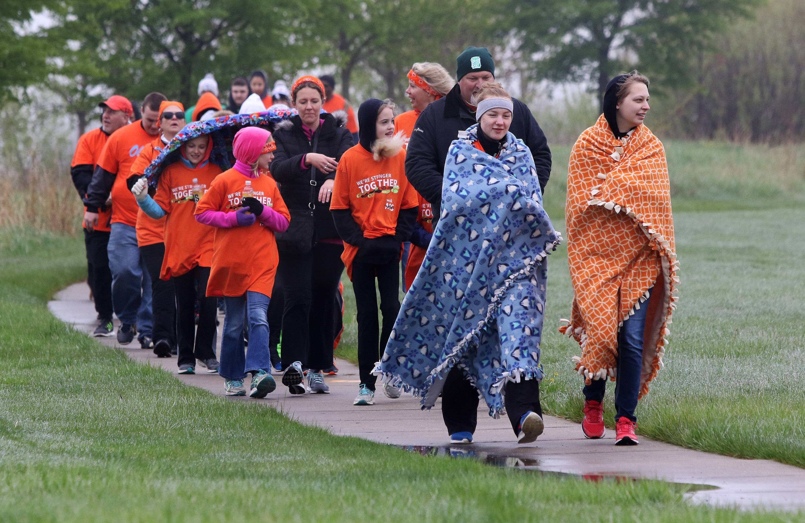 Johanna Duckmann, 16, of Des Plaines, left, and Isabella Markworth, 15, of Mount Prospect try to stay warm as they walk with the crowd during the Walk MS Northwest Suburbs on Sunday starting at Cabela's in Hoffman Estates. More than 1,000 people bundled up to walk in the misty morning to help raise money for multiple sclerosis research.