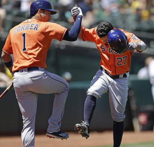Houston Astros' Jose Altuve, right, celebrates with Carlos Correa (1) after hitting a home run off Oakland Athletics' Rich Hill in the first inning of a baseball game Sunday, May 1, 2016, in Oakland, Calif.