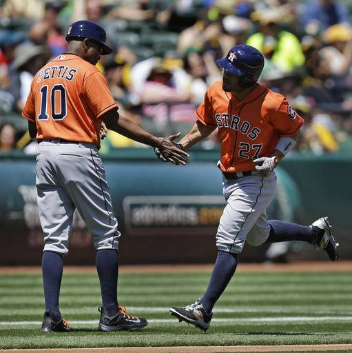 Houston Astros' Jose Altuve, right, celebrates with third base coach Gary Pettis (10) after hitting a home run off Oakland Athletics' Rich Hill in the first inning of a baseball game, Sunday, May 1, 2016, in Oakland, Calif.