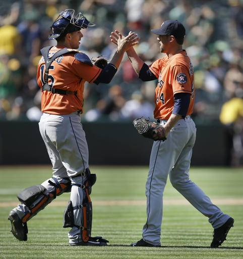 Houston Astros pitcher Luke Gregerson, right, and catcher Jason Castro celebrate their victory over the Oakland Athletics in  a baseball game Sunday, May 1, 2016, in Oakland, Calif.