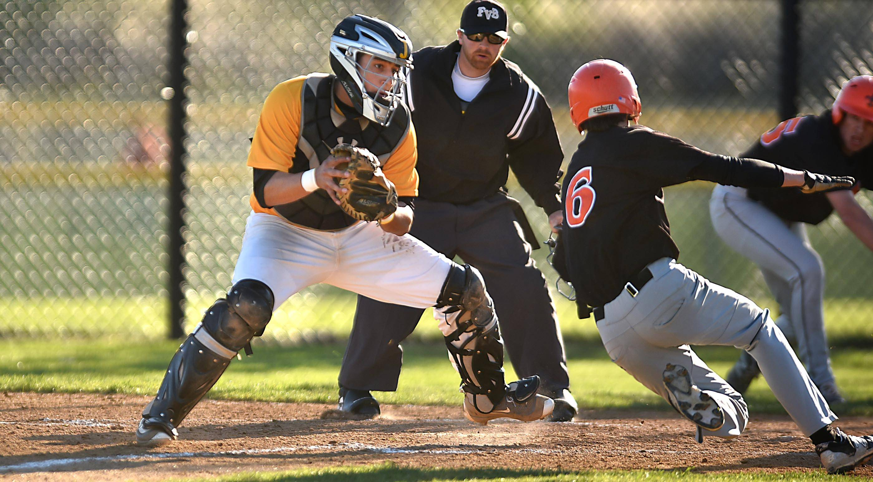 Jacobs catcher Dan Salomon steps in front of the plate to tag out St. Charles East's John Caroll for the first out of the fifth inning Monday in Algonquin.