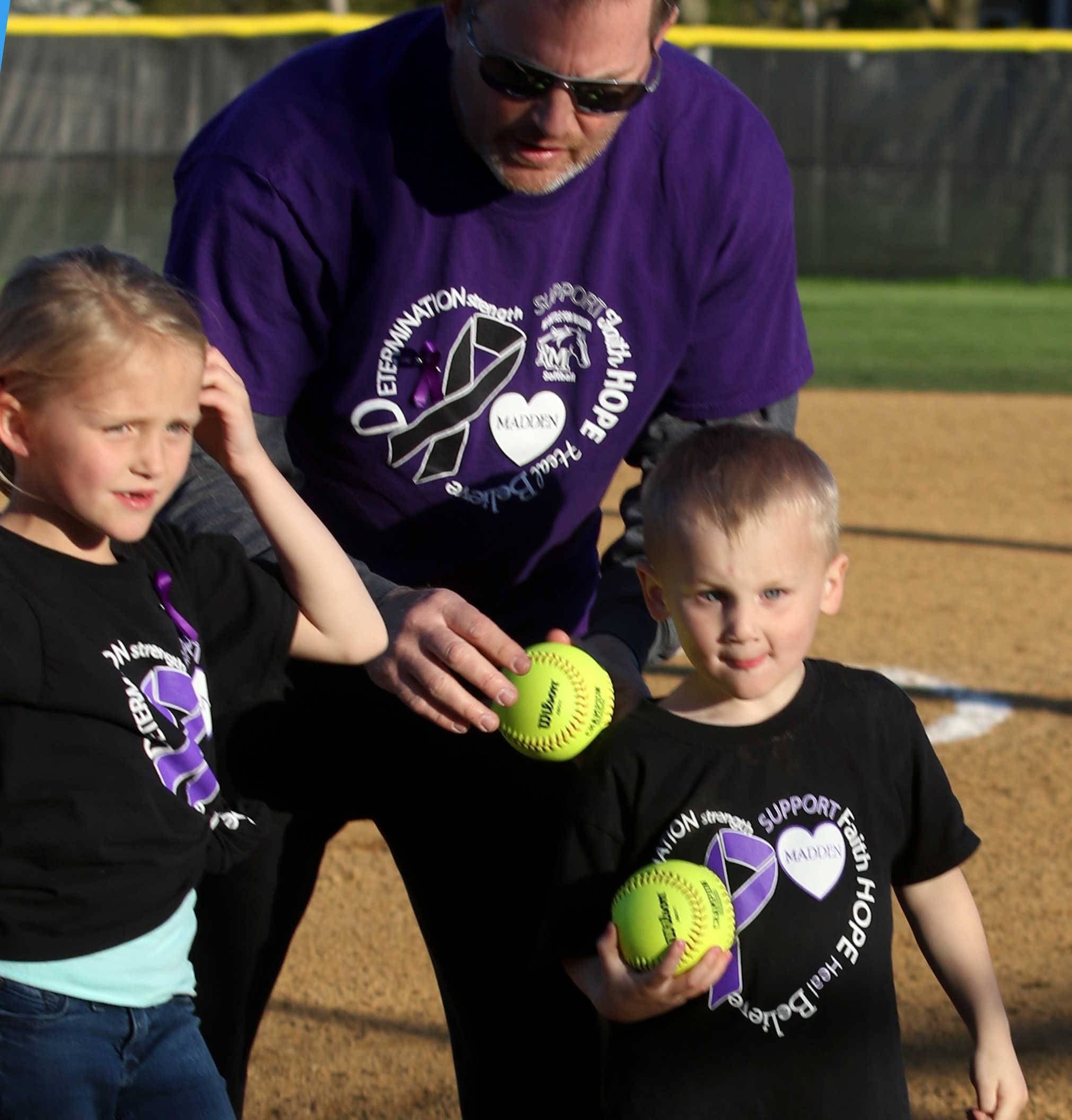 Maive Manz, 6, and her brother Max, 4, children of Rolling Meadows assistant coach Jeff Manz, center, prepare to toss out ceremonial first pitches as part of a special doubleheader of varsity softball games at Rolling Meadows High School on Monday. Fremd won 5-0 over Hersey in game one while Rolling Meadows played Palatine in the second game. The Manz children tossed out ceremonial first pitches in honor of their younger brother, Madden, who is being treated for Rett Syndrome.