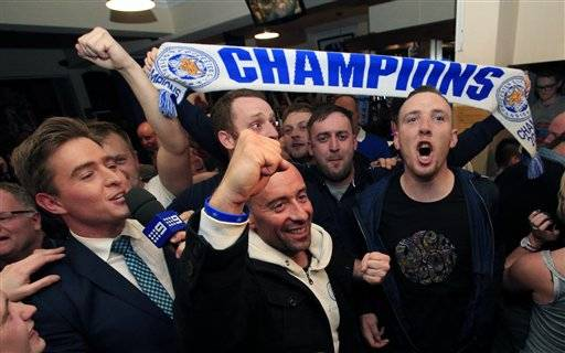 Leicester City fans celebrate in the Market Tavern in Leicester after seeing their side crowned English Premier League soccer champions following Tottenham Hotspur's 2-2 draw against Chelsea. The match resulted in Leicester City winning the Premier League, Monday May 2, 2016. (Jonathan Brady/PA via AP) UNITED KINGDOM OUT