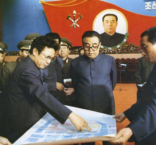 In this October 1980 photo provided by the Korea News Service (KNS), then North Korean leader Kim Il Sung, center, and his son Kim Jong Il, left, talk about the preparation for the convention of North Korea's Workers' Party in Pyongyang, North Korea. North Korea, the world's last great master of socialist spectacle, is likely to deliver a big one when its ruling party holds its first congress in 36 years later this week, scheduled to begin on Friday, May 6, 2016. (Korea News Service via AP) JAPAN OUT UNTIL 14 DAYS AFTER THE DAY OF TRANSMISSION