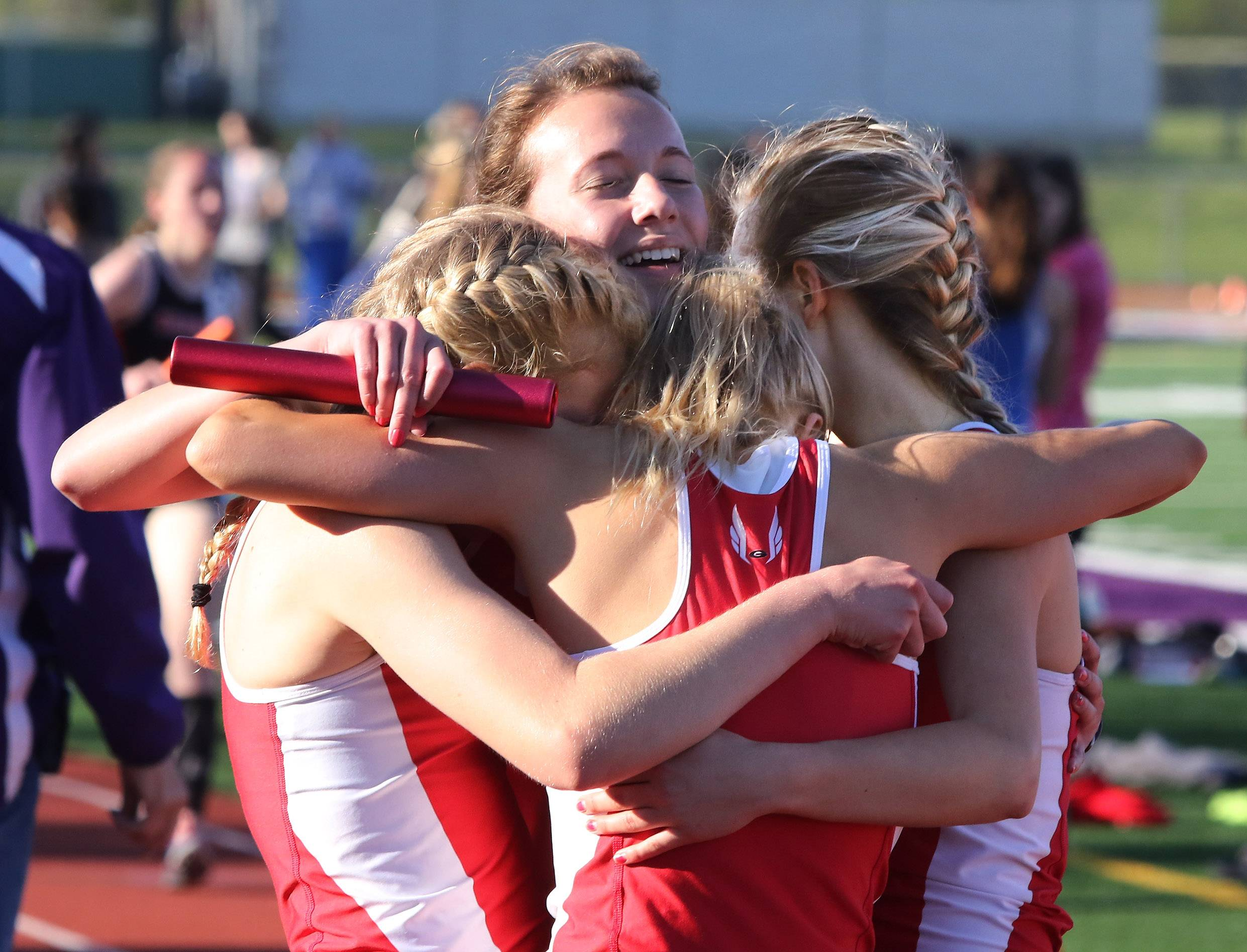 Grant's 4x800 relay team with Madison Romig, above everyone, hugs it out after winning the race during the North Suburban Conference meet Thursday at Wauconda.
