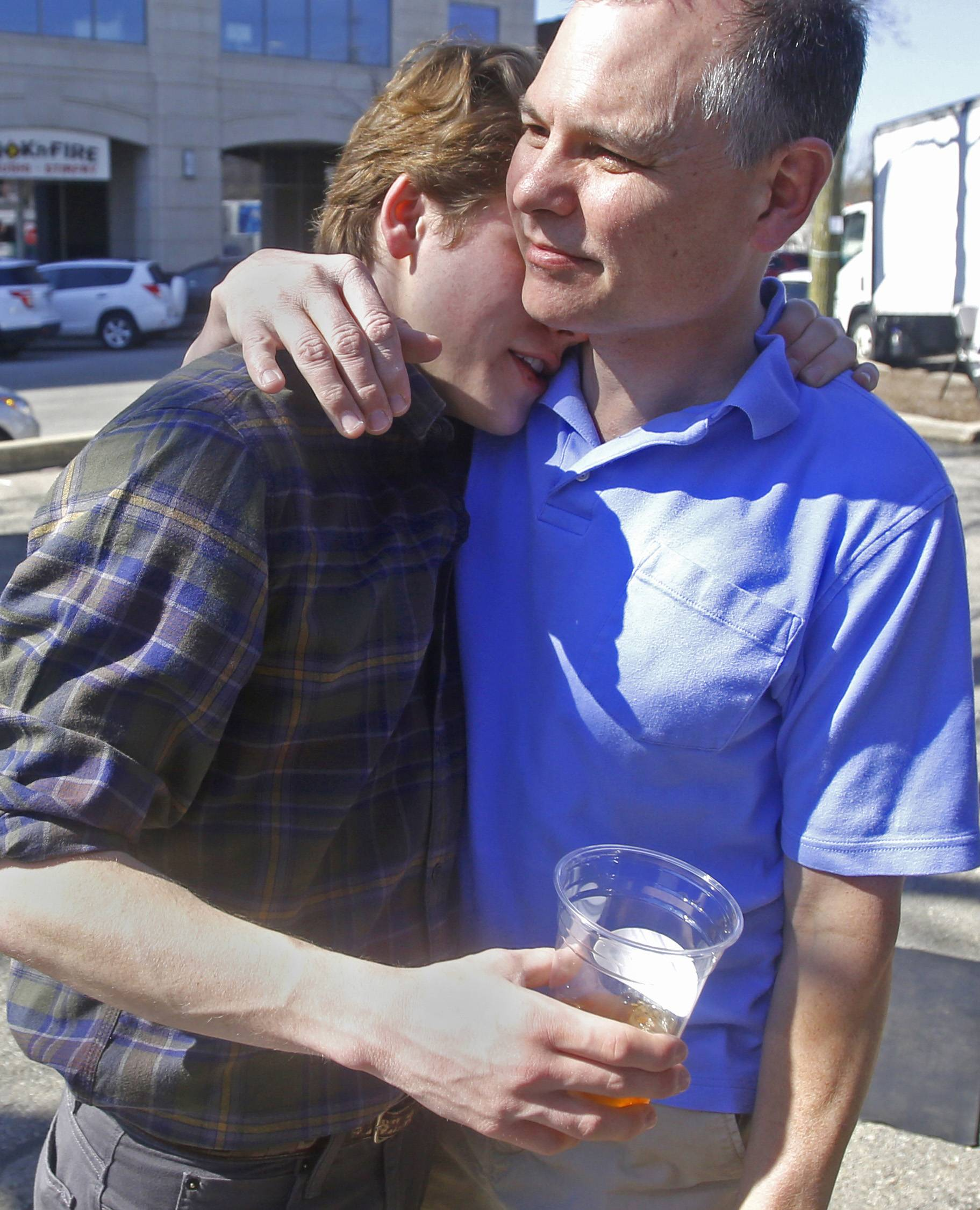 Pete Leonard, right, hugs his son Sam outside the I Have a Bean booth at the French Market, a popular Saturday morning stop in downtown Wheaton.