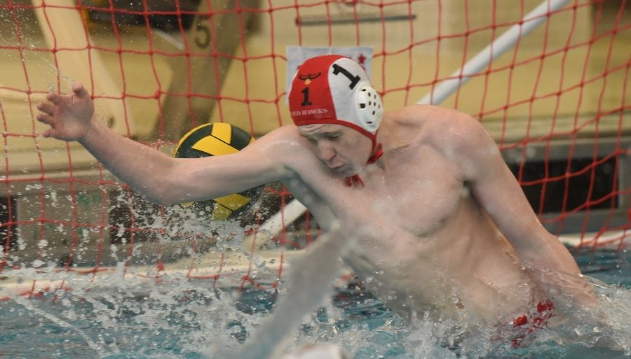 Naperville Central goalkeeper Kent Emden gets just enough of a Stevenson shot to keep it from going in for a goal during Saturday's boys water polo match in Lincolnshire. The Redhawks won 9-4.
