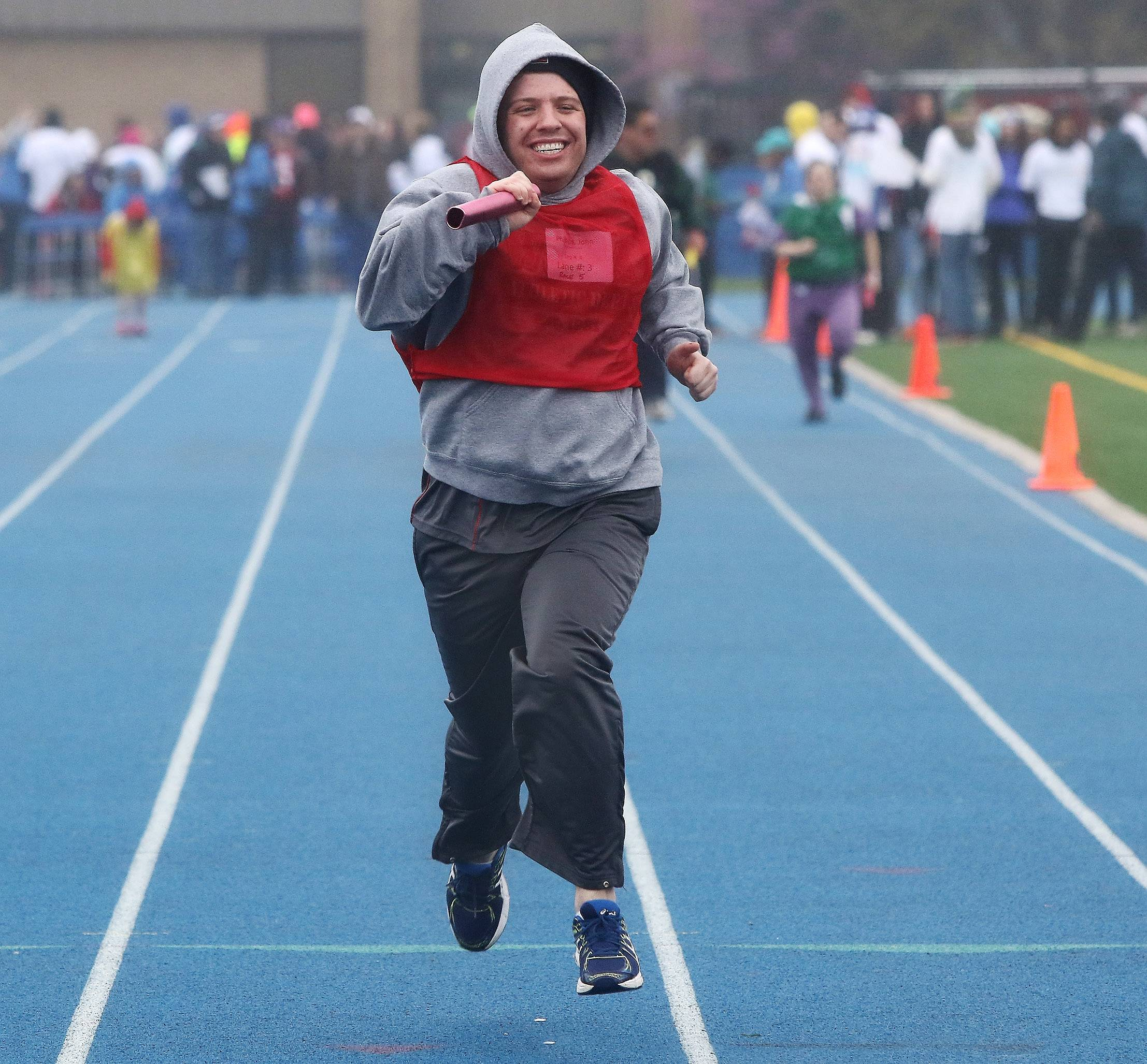 John Phillips, of Warren SRA is all smiles as he crosses the finish line after competing in the 4x100 meter relay during the annual Spring Games of Special Olympics Illinois Northeastern/Area 13 on Sunday at Lake Zurich High School. As a light drizzle fell on the field, Special Olympics athletes competed in races on the wet track.