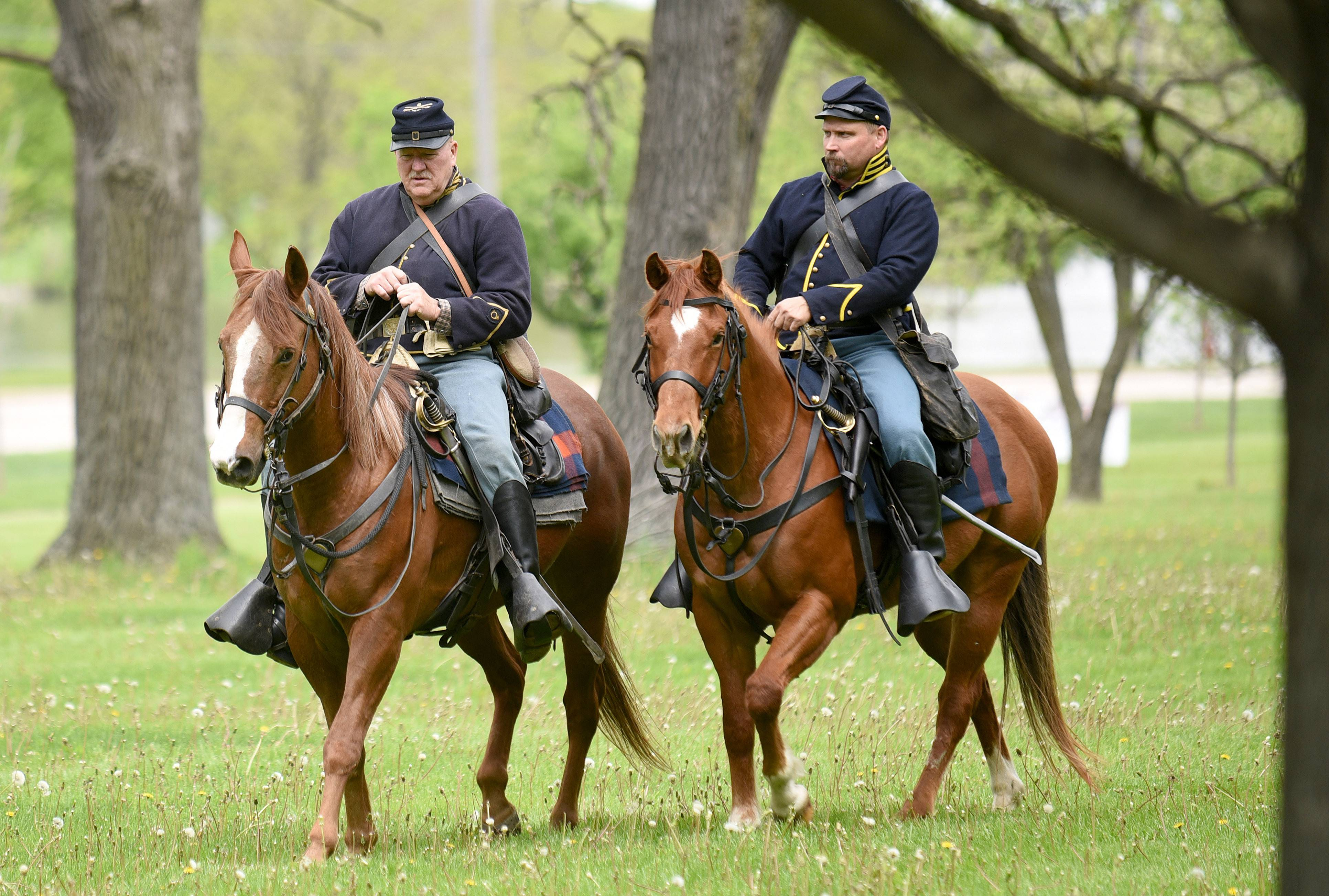 "8th Illinois Volunteer Cavalry Regiment re-enactor Roland Wood of Wonder Lake and his horse, Champ (left) and Garth Kisel of Yorkville on his horse, Colonel, ride through Langum Park in St. Charles during the Camp Kane Heritage Foundation and the 8th Illinois Volunteer Cavalry Regiment's ""Train the Troops"" day Saturday."