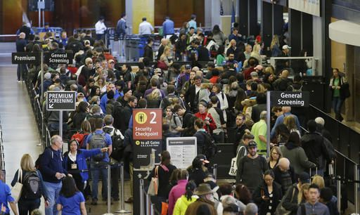 FILE - In this March 17, 2016, file photo, travelers wait in line for security screening at Seattle-Tacoma International Airport in Seattle. Two U.S. senators say the way to reduce long airport security lines this summer is for airlines to drop their fees on checking luggage. Massachusetts Democrat Edward Markey and Connecticut Democrat Richard Blumenthal said Tuesday, May 10, 2016, they asked executives at 12 airlines to drop checked-bag fees this summer. The senators say suspending the fees won't eliminate lines but it's a start.