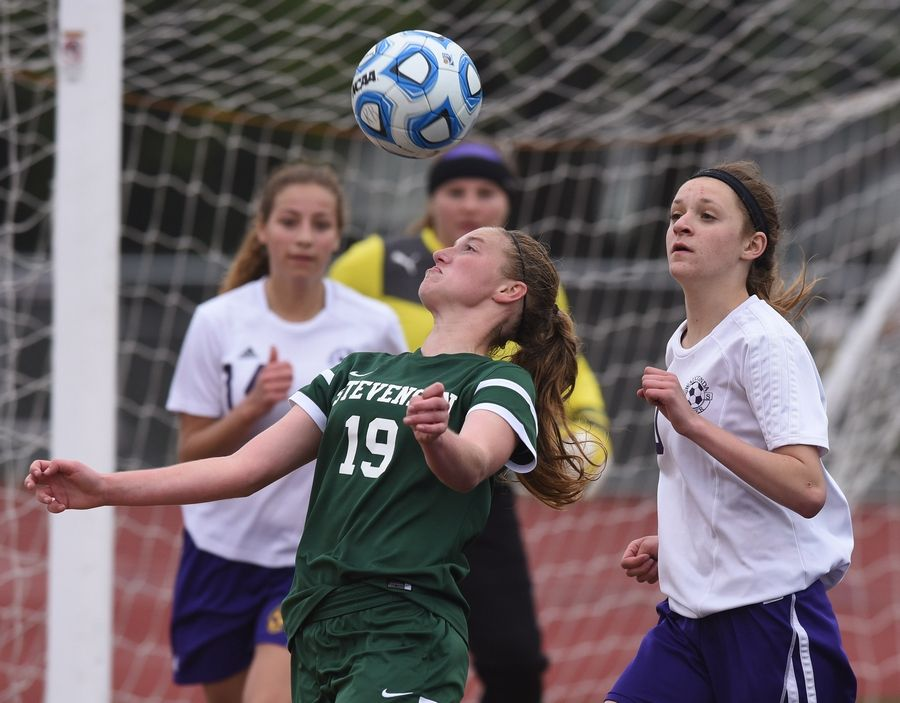 Stevenson's Hannah Lapeire, left, tries to gain control the ball in front of Wauconda's Abigail McHugh, right, and the Bulldog's net during the North Suburban Conference championship game at Wauconda on Tuesday.