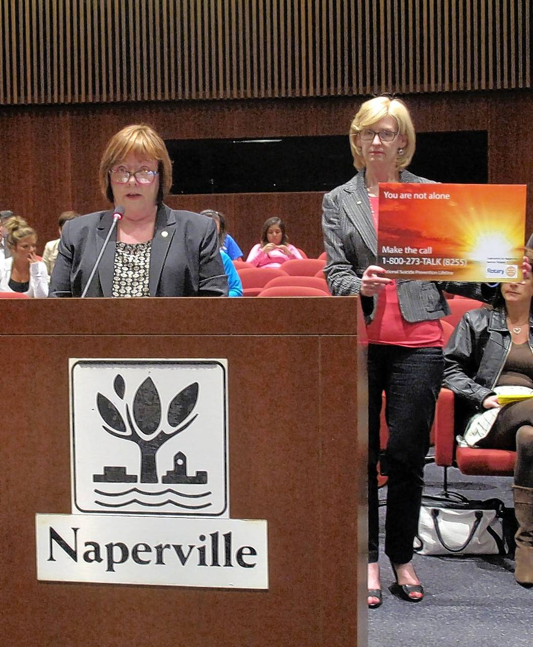Dr. Caroline Morrison discusses the Rotary Club of Naperville Sunrise's campaign to post suicide prevention signs at the Naperville 5th Avenue Metra station while club member Cathy Goulet shows one of the signs to Naperville City Council members.