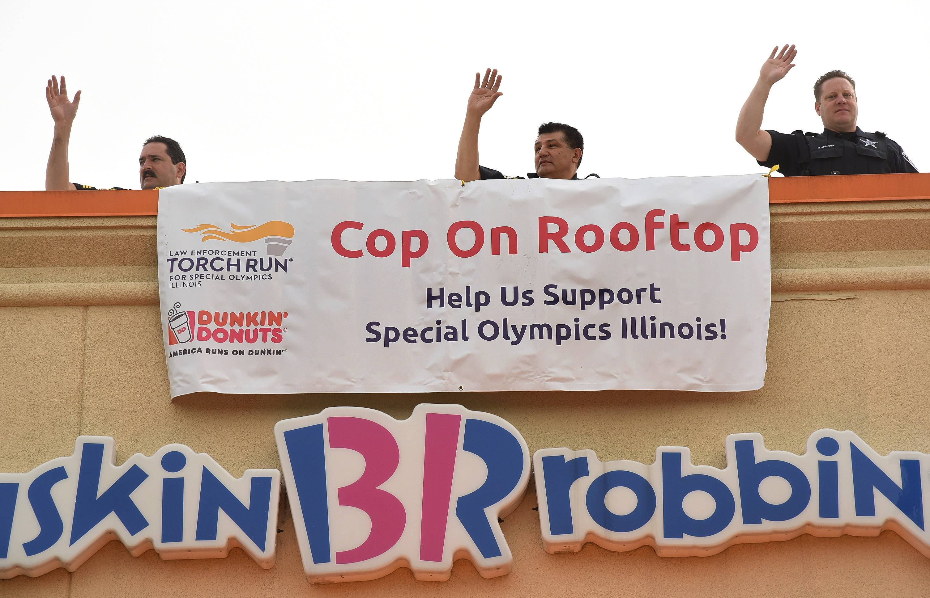 Arlington Heights Police from left, Sgt. Rick Boyle, Deputy Chief Mike Hernandez, and Officer Russell Mandel wave from atop the Dunkin' Donuts location on Rand Road in Arlington Heights, during Dunkin' Donuts Cop on a Rooftop event.