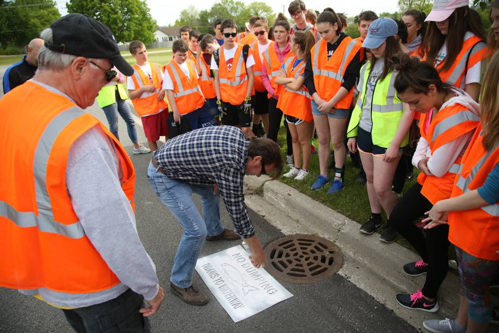 Lake Zurich Public Works Manager Mike Brown demonstrates the stenciling process to Lake Zurich Middle School South eighth grade students as part of a storm drain stenciling event Friday. The stenciling aims to remind the public that drainage inlets are for stormwater only.